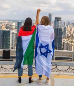 Young Israeli and Emirati wearing UAE & Israel flages